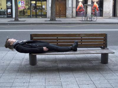 jeune femme allongée en porte à faux sur un banc