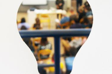 vue floutée d'une conférence à travers un masque en forme d'ampoule
